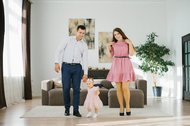 La familia feliz con la pequeña hija se divierte pasando su tiempo libre en su apartamento Foto Premium