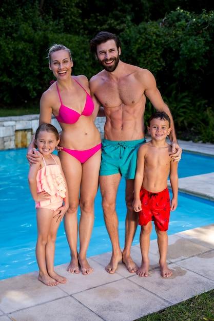 Familia feliz de pie junto a la piscina Foto Premium