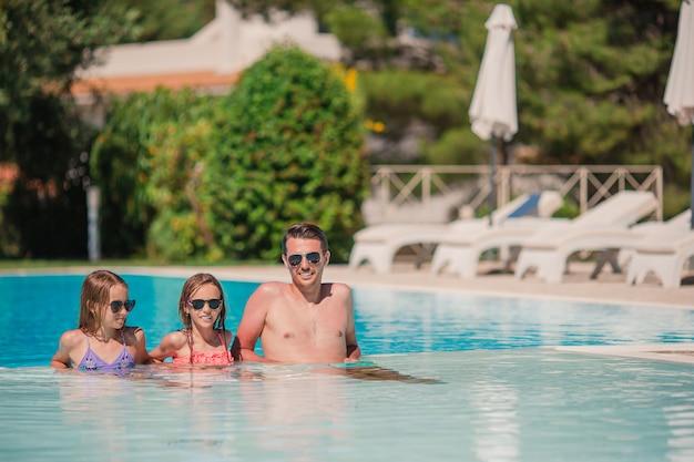 Familia feliz en la piscina al aire libre Foto Premium