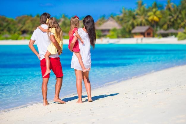 Familia feliz en la playa blanca durante las vacaciones de verano Foto Premium