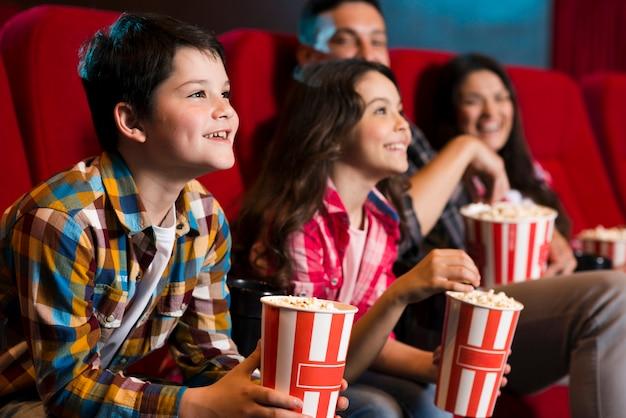 Familia feliz sentada en cine Foto gratis