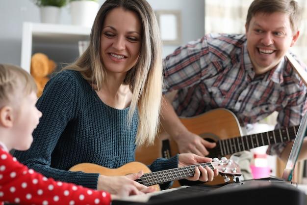 Familia feliz toca instrumentos musicales en el fondo Foto Premium
