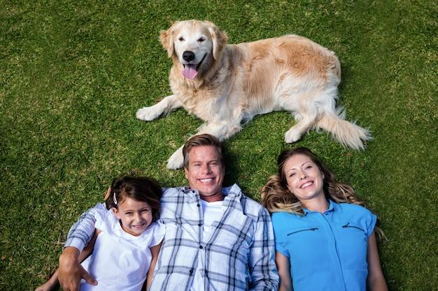 Familia feliz tumbado ion hierba con su perro Foto Premium