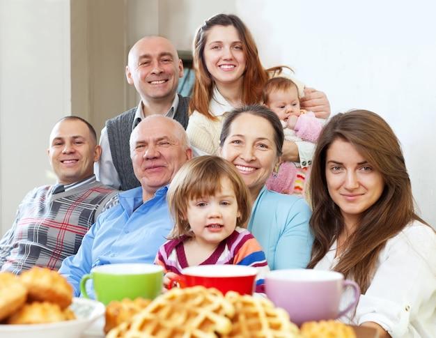 Familia grande feliz tomando el té Foto gratis
