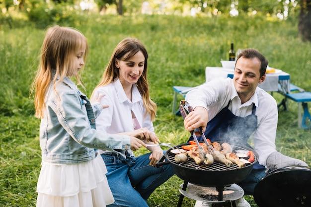 Familia haciendo una barbacoa en la naturaleza Foto gratis