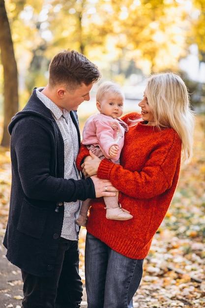 Familia con hija bebé caminando en un parque de otoño Foto gratis