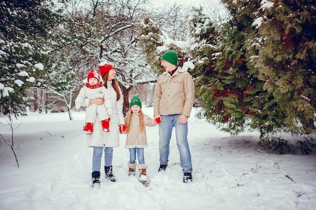 Familia con hijas lindas en un parque de invierno Foto gratis