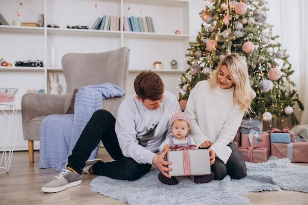 Familia con hijita desempacando regalos por árbol de navidad Foto gratis