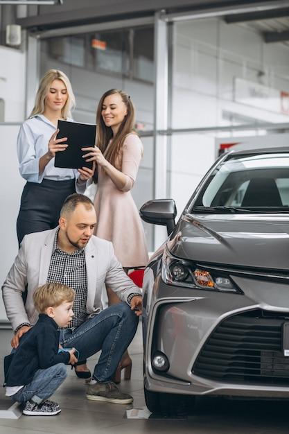 Familia con hijo elegir un coche en una sala de exposición de coches Foto gratis
