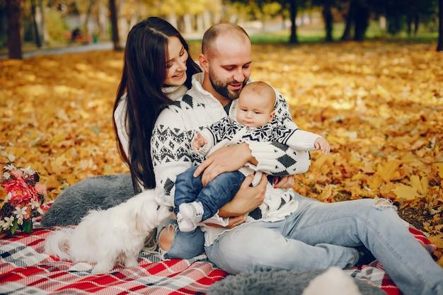 Familia con hijo en un parque de otoño Foto gratis