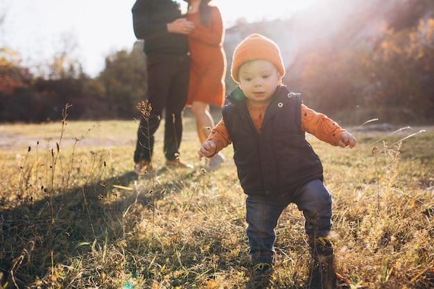 Familia con un hijo pequeño en el parque otoño Foto gratis