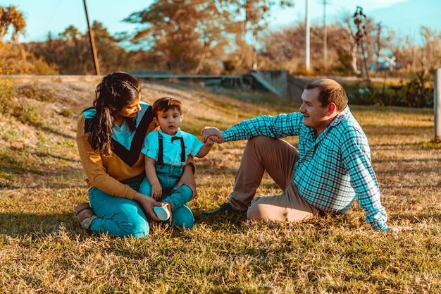 Familia con hijo sentado en la hierba Foto Premium