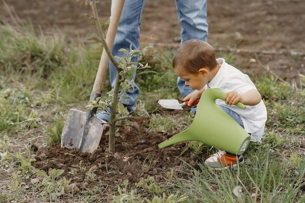 Familia con hijos pequeños están plantando un árbol en un patio Foto gratis