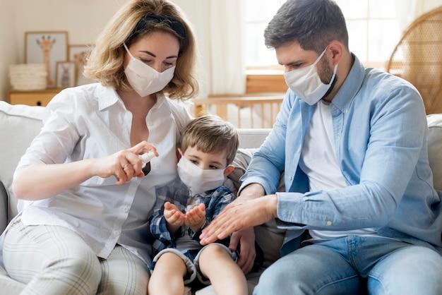 Familia en interiores usando desinfectante y usando máscaras médicas Foto Premium