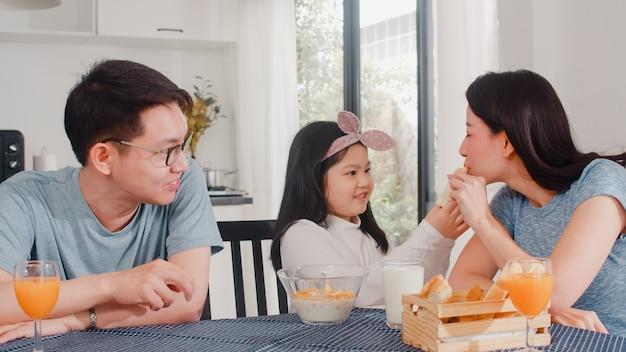 Familia japonesa asiática desayuna en casa. asia mamá, papá e hija se sienten felices hablando juntos mientras comen pan, cereales y leche en un tazón sobre la mesa en la cocina por la mañana. Foto gratis