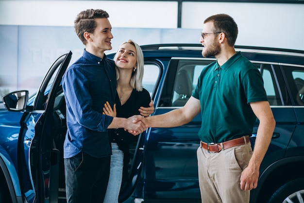 Familia joven comprando un automóvil en una sala de exposición de automóviles Foto gratis