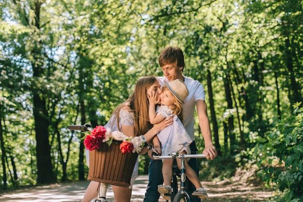 Familia joven feliz pasar tiempo juntos afuera. padre madre y su hijo en el parque verde en un picnic. Foto Premium