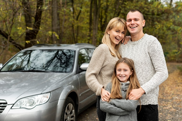 Familia joven feliz posando junto a un automóvil Foto gratis
