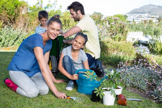 Familia joven feliz que cultiva un huerto junto   Foto Premium