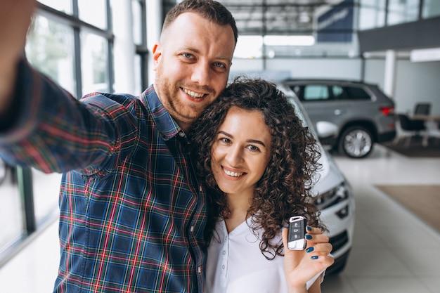 Familia joven haciendo selfie en una sala de exhibición de autos Foto gratis