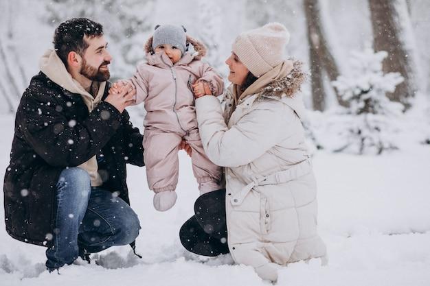 Familia joven con hija pequeña en un bosque de invierno lleno de nieve Foto gratis