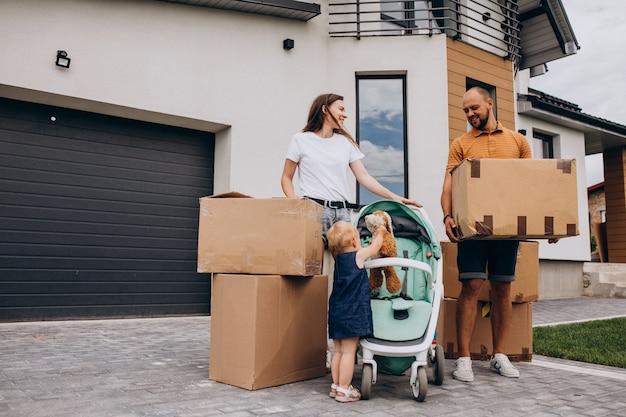 Familia joven con hija pequeña mudarse a casa nueva Foto gratis