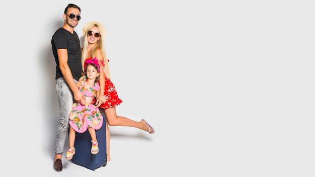 Familia joven con maleta Foto gratis
