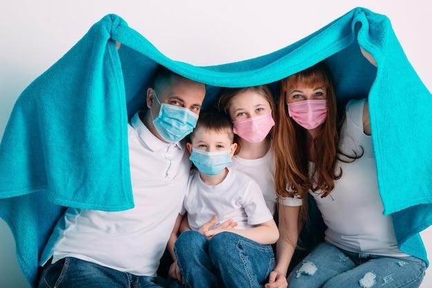 Familia joven en máscaras médicas durante la cuarentena domiciliaria. Foto Premium