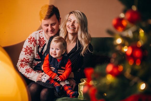 Familia joven con niña sentada junto a árbol de navidad Foto gratis