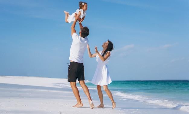 Familia joven con pequeña hija en vacaciones junto al mar Foto gratis