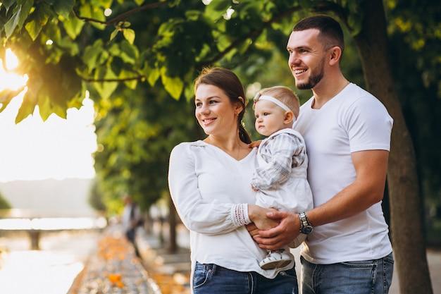 Familia joven con su pequeña hija en el parque otoño Foto gratis