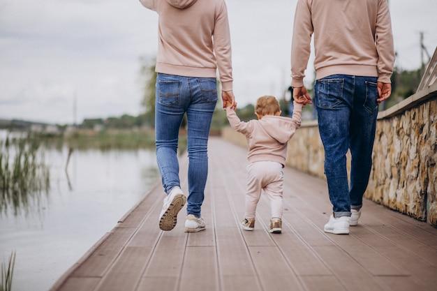 Familia joven con su pequeño hijo bebé en el parque junto al lago Foto gratis