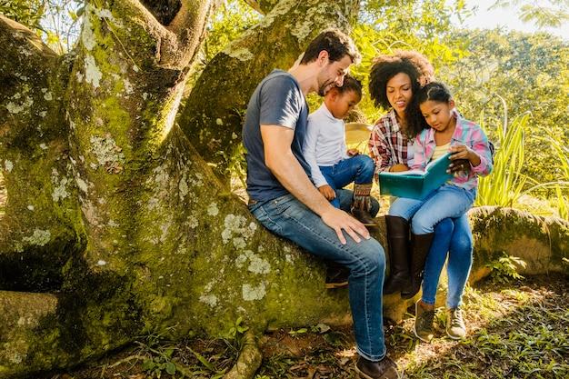 Familia leyendo juntos en un tronco de árbol Foto gratis