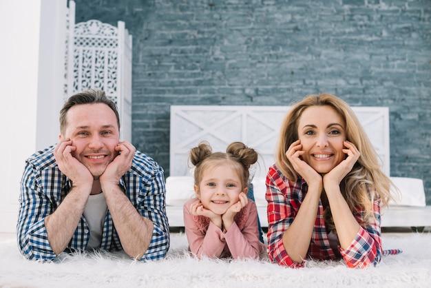 Familia linda alegre que miente en la alfombra que mira la cámara Foto gratis