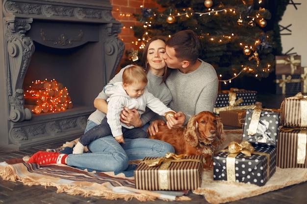 Familia con lindo perro en casa cerca del árbol de navidad Foto gratis