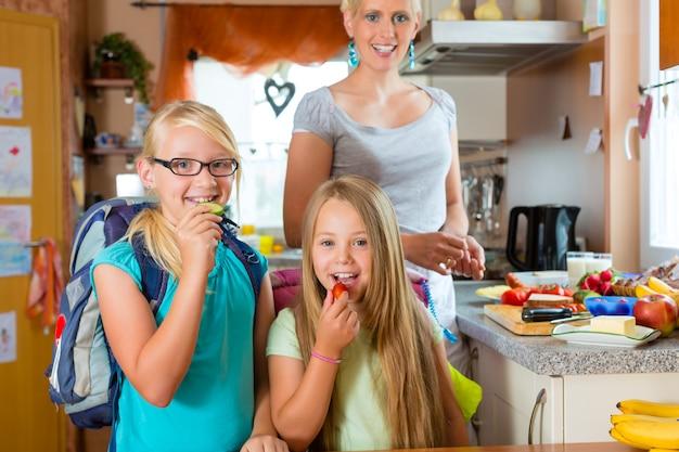 Familia, madre preparando el desayuno para la escuela Foto Premium
