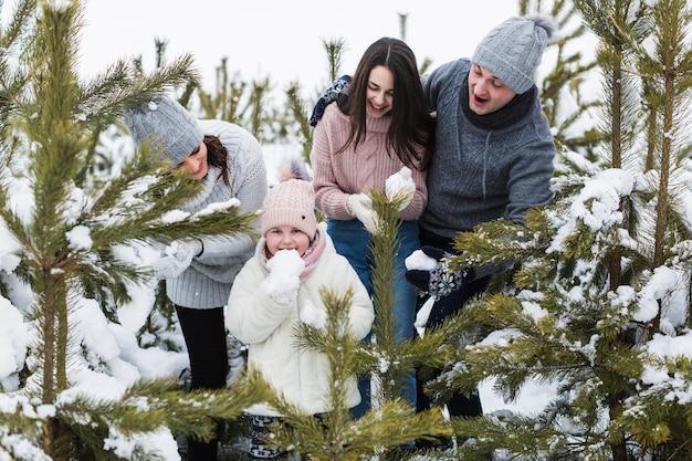 Familia mirando niña comiendo nieve Foto gratis