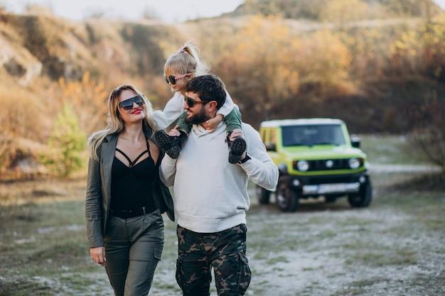 Familia moderna joven que viajaba en coche y se detuvo a caminar en el parque Foto gratis