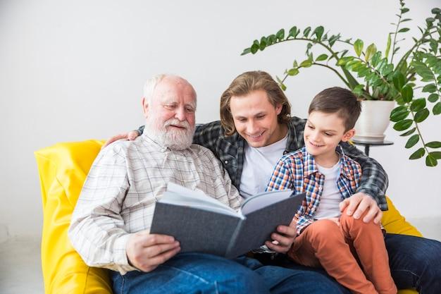 Familia multigeneracional mirando a través del antiguo álbum de fotos. Foto gratis