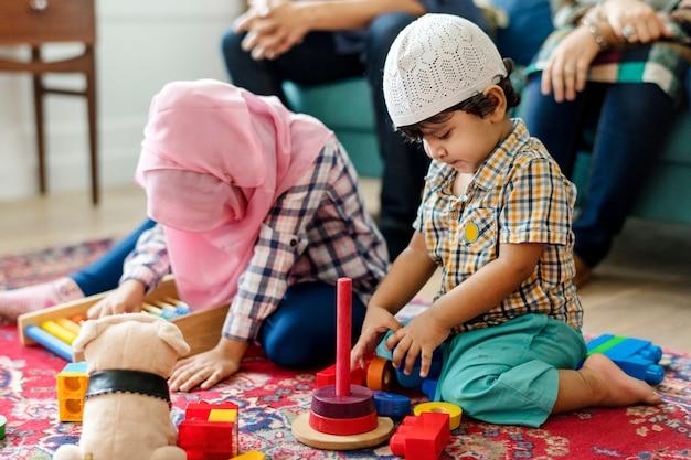 Familia musulmana relajante y jugando en casa Foto Premium