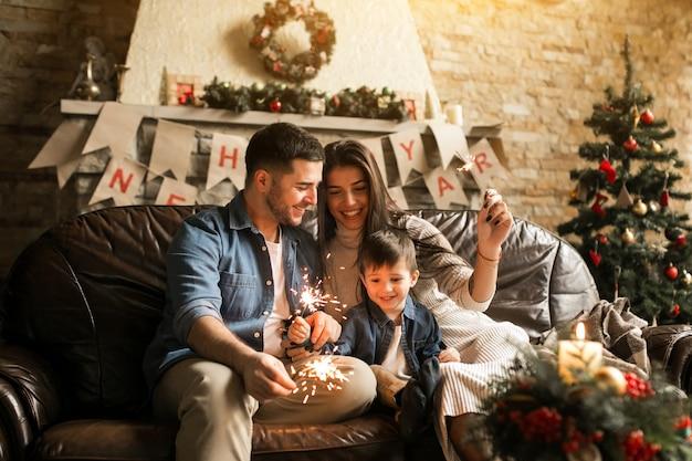 Familia en navidad con luces de bengala Foto gratis