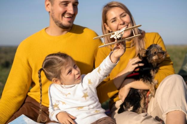 Familia con niño y perro jugando con juguete de avión Foto gratis