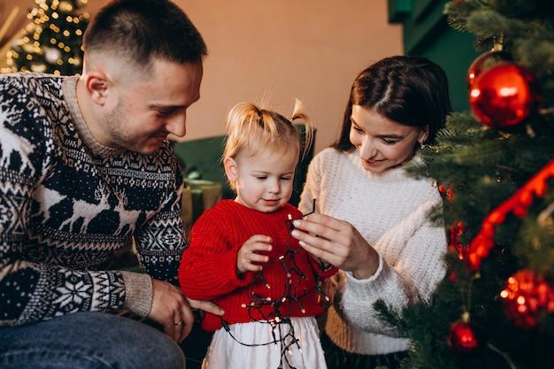 Familia con pequeña hija colgando juguetes en el árbol de navidad Foto gratis