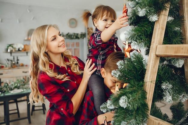Familia de pie en casa cerca del árbol de navidad Foto gratis
