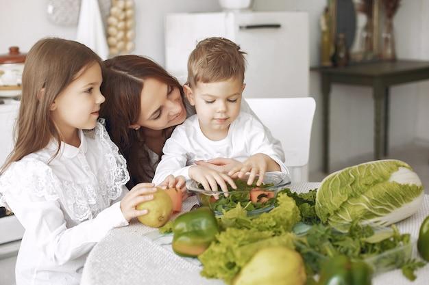 Familia preparando una ensalada en una cocina Foto gratis