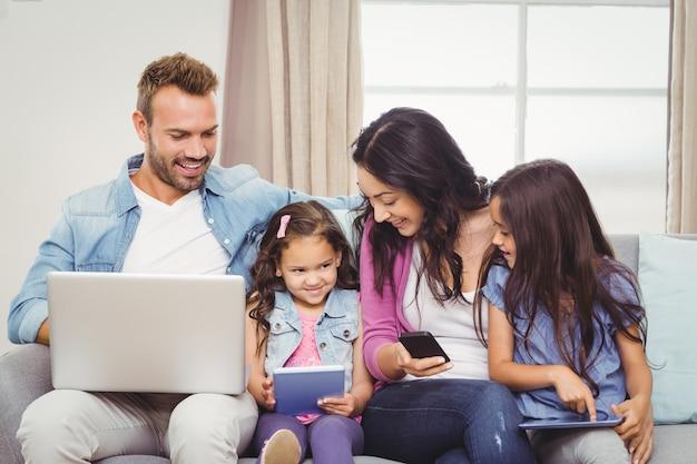 Familia que usa tecnologías modernas en el sofá Foto Premium