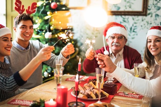 Familia con quema de fuegos de bengala en mesa festiva Foto gratis