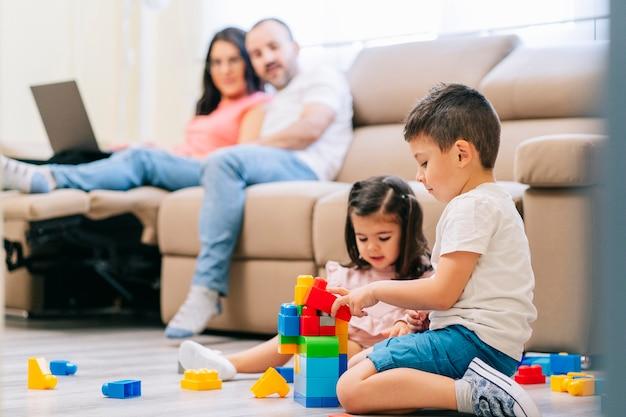 Una familia en la sala de estar, los padres trabajan a distancia con la computadora y los niños juegan en el piso. Foto Premium