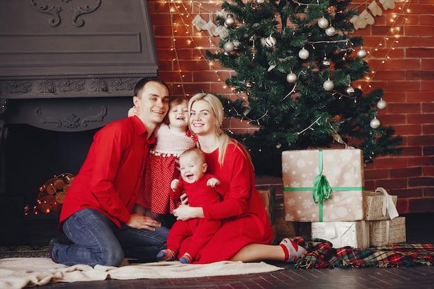 Familia sentada en casa cerca del árbol de navidad Foto gratis