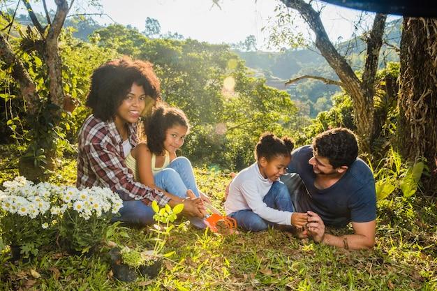 Familia sentada en el cesped Foto gratis